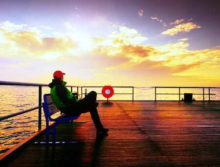 Man hiker on mole at sea. Tourist on wharf looking ower sea to horizon. Sunny clear blue sky, smooth water level Stock Photo