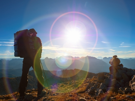 rocky peak: Lens flare light, strong defect. Man hiker with rucksack walk  on rocky peak. Tourist  walking over rocky summit to Sun. Beautiful moment the miracle of nature.