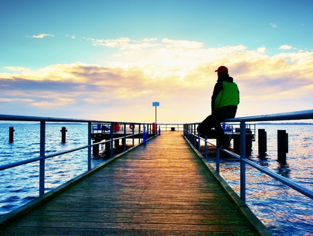 warm jacket: Man in warm jacket and baseball cap sit on pier and enjoy quiet morning sea. Tourist relax. Sunny clear blue sky, smooth water level
