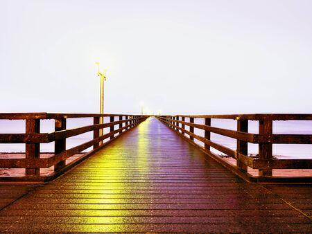 Autumn misty morning on wooden pier above sea. Depression, dark atmosphere. Touristic mole, wet wooden floor above sea.
