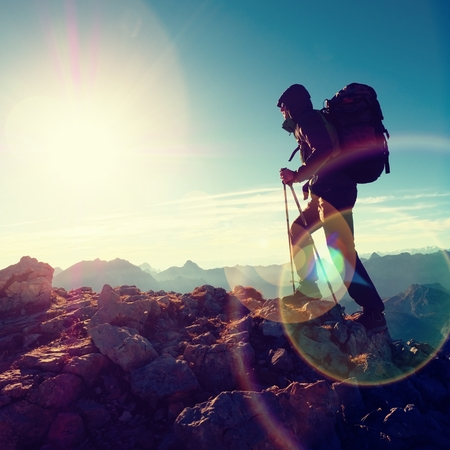 rocky peak: Lens flare light, strong defect. Silhouette of man with hood, backpack and poles in hand. Man walk on rocky peak of mountain. Sunny day rocky mountains.