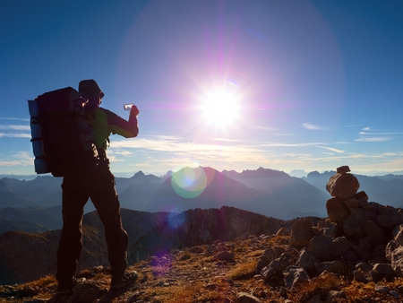 Lens flare light, strong defect. Hiker takes selfie photo. Man with big backpack and poles walk on Alpine mountain. Sun above  horizon blue foggy valley. Mountains increased from humidity