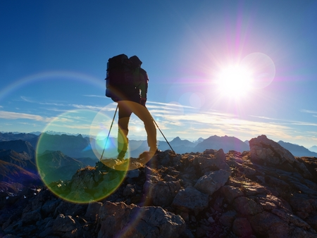 Lens flare light, strong defect. Silhouette of man with hood,backpack and poles in hand. Man walk on rocky peak of mountain. Sunny day rocky mountains. Stock Photo