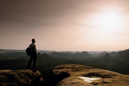 marvelous: Man hiker  at mountain peak. Marvelous daybreak in autumn misty landscape. Sun above horizon.