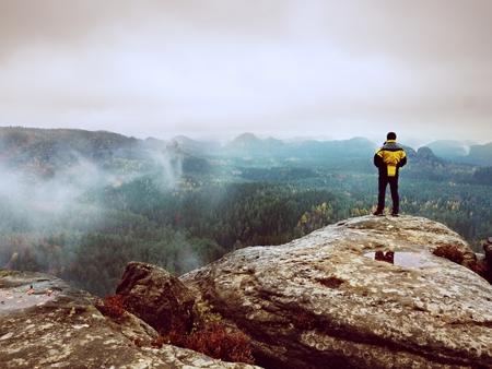 山の谷の上の夜明けを楽しみながら岩が多い峰の黄色黒のジャケットの男性ハイカーの後姿