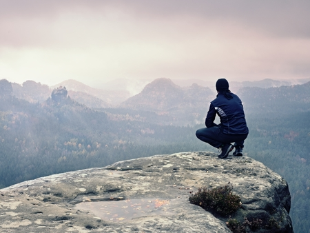 Adult tourist in black trousers, jacket and cap sit on cliffs edge looking to misty hilly valley bellow. Foggy autumn weather. Wet rock withfallen  autumn leaves Stock Photo