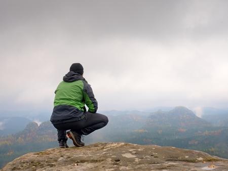 en cuclillas: Turista en la gorra roja y ropa deportiva negro verde en la posición en cuclillas sobre una roca, disfrutar de un paisaje de otoño. Largo valle lleno de niebla cremosa pesado después de noche de lluvia