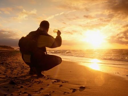 en cuclillas: El hombre toma la foto del mar de la tarde. Caminante con el morral con el teléfono en la mano. Turista sentarse en cuclillas possition largo de la playa. Estilo Vintage efecto virada Foto de archivo