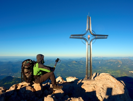 Tired hiker sit bellow crucifix on mountain peak. Iron Cross at Alps mountain top. Relaxing tourist with poles and heavy backpack