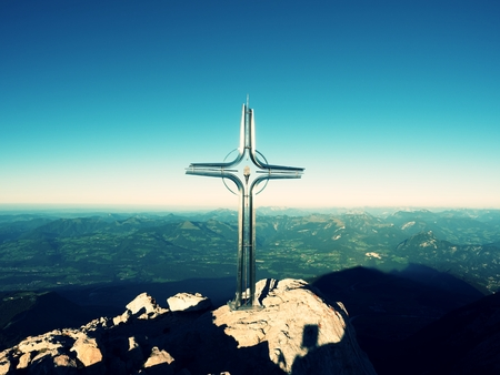 Cross with semi-precious stone raised  at mountain summit  in Alps. Sharp peak. Daybreak Sun in sky. Steel crucifix in memory of victims of mountains. Vivid photo. Stock Photo