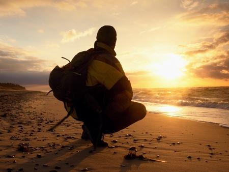en cuclillas: El hombre se sienta en el mar por la noche. Caminante con mochila sentarse en cuclillas possition largo de la playa. Estilo Vintage efecto virada