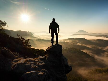 rocky peak: The man standing on a high cliff. Hiker climbed up a rocky peak and enjoy view this valley bellow. Man watch over misty and foggy morning valley in morning Sun. Stock Photo