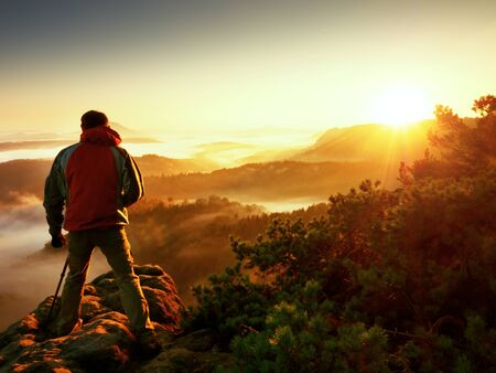 Photograph silhouette  take photo. Man enjoy  photography of  fall daybreak in nature on cliff on rock. Autumnal foggy landscape, misty sunrise.