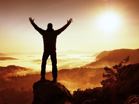 Herfst nevelige ochtend in de natuur. Wandelaar in het zwart staan op de piek in rock en waakt over de nevelige en mistige ochtend van Sun Valley