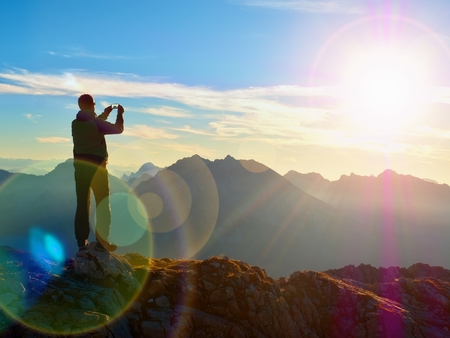 Lens flare light, strong effect. Bow light circles.  Hiker takes selfie photo. Tourist at mountain peak. Daybreak horizon above blue foggy valley. Mountains increased from humidity