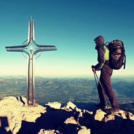 Hiker at the big crucifix on mountain peak. Iron Cross at Alps mountain top. Tourist with poles and heavy backpack Stock Photo