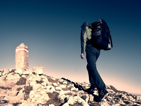 Hiker with backpack climbing on mountain peak. Stone Summit at Alps mountain top. Tourist walk with heavy backpack Stock Photo