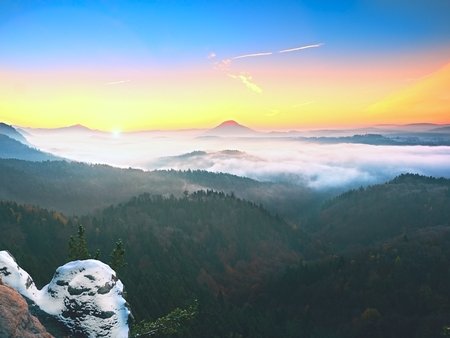 Cocks covered with fresh powder snow, misty valley. Stony rock peak increased from foggy valley. Winter misty sunrise in a beautiful rocks empire. Stock Photo