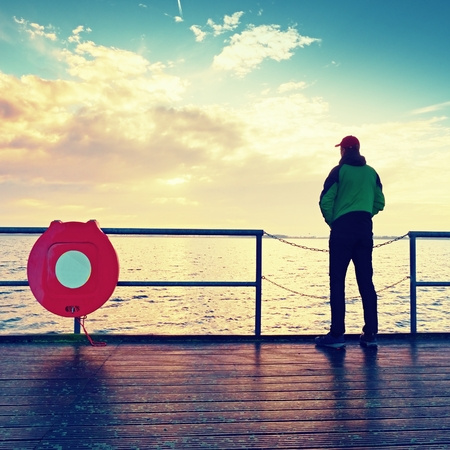 Alone man on pier and look over handrail into water. Sunny sky, smooth water level. Vivid and strong vignetting effect