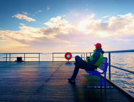 Man in warm jacket and baseball cap sit on mole bench and enjoy morning at sea. Sunny clear blue sky, smooth water level
