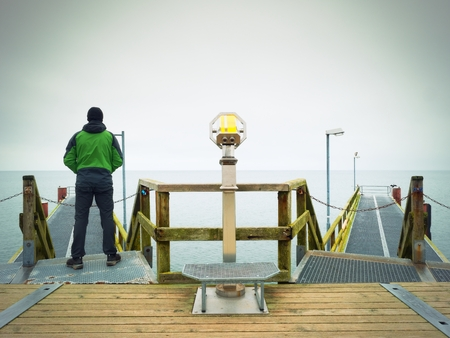 constrution: Man on long touristic pier, cold autumn morning. Tourist at handrail. Wet wooden board, constrution above sea smooth.