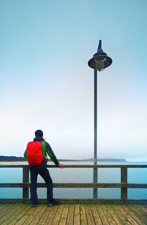 dejection: Man tourist in autumn mist on wooden pier above sea. Depression, dark atmosphere. Touristic mole, wet wooden floor above sea.