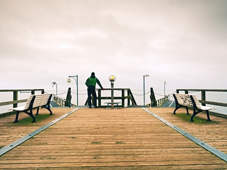 dejection: Man on wooden pier in harbor within The misty autumn day. Tourist at handrail. Wet wooden board, constrution above sea smooth.
