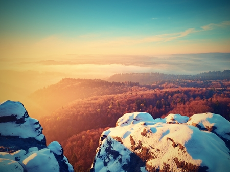 inversion: Freeze daybreak, rocks covered with fresh powder snow. Stony rock peak above foggy valley. Winter misty sunrise in a beautiful rocks empire.