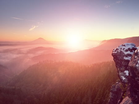 first miracle: Pink daybreak in hilly landscape. Early winter misty morning in  beautiful rocky hills. Peaks of hills in heavy fog. Miracle of nature Stock Photo