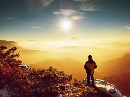 Tall hiker in black on rocky peak watch the world . Heavy orange mist bellow in valley. Wonderful breathtaking daybreak in mountains. Stock Photo