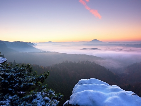 damping: Freeze autumnal daybreak, rocks covered with fresh powder snow. Stony rock peak high damping from foggy valley. Winter misty sunrise in a beautiful rocks empire. Stock Photo