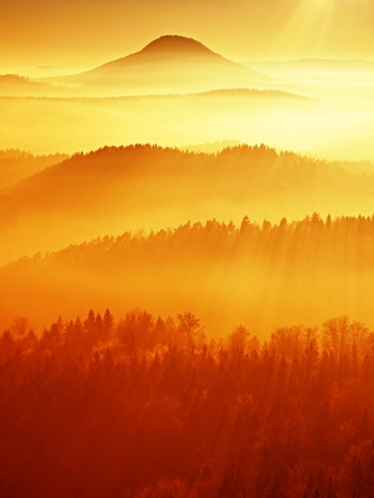 Red filter photo. Red daybreak. Misty daybreak in a beautiful hills. Peaks of hills are sticking out from foggy background, the fog is red and orange Stock Photo