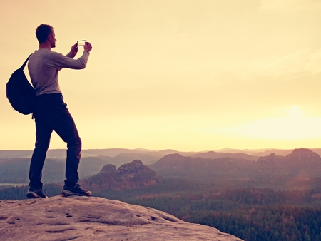 marvelous: Sportsman take selfie photo with phone at mountain peak. Man with phone in hand. Misty mountains at horizon. Marvelous daybreak.