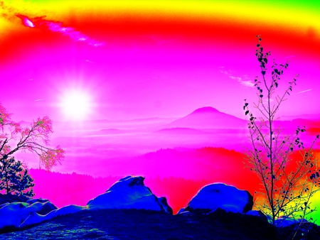 Ultraviolet  scan. Infrared  photo. Freeze autumnal daybreak, rocks covered with fresh powder snow. Stony rock peak increased from fog Stock Photo