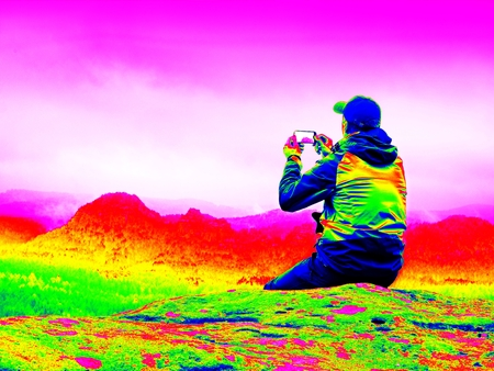 Ultraviolet  scan. Infrared  photo. Young man in black sportswear on cliff edge and looking to misty valley bellow. Autumn cold weather