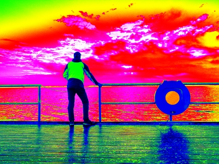 Ultraviolet  scan. Infrared  photo.  Man stand at handrail on mole and looking over sea to morning horizon.