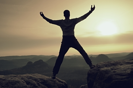 a situation alone: Happy man with raised arms gesture triumph on exposed cliff. Satisfy hiker silhouette on sandstone cliff watching down to hilly landscape.