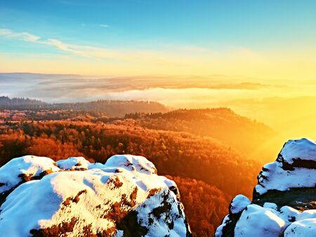 Chilli day in rocks. Rocky peak of sandstone mountain in sunny winter day. Frozen Twigs and rock under fresh powder snow. Stock Photo