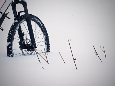 The front wheel of mountain bike stay in powder snow. Lost path under deep snowdrift. Snow flakes melting on dark off road tyre.  Winter weather in the field.
