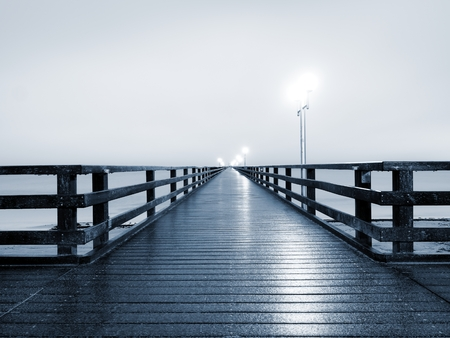 shinning light: Autumn misty morning on wooden pier above sea. Depression, dark atmosphere. Touristic mole, wet wooden floor above sea.