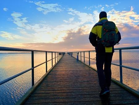 桟橋や水の中に手すりを見るだけで男は。晴れた空、滑らかな水レベル。鮮やかで強い効果をケラレ