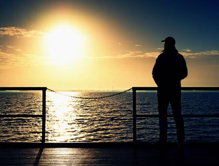 Adult tall man on pier board look over sea to morning Sun. Smooth water level in bay. Vivid and strong vignetting effect.