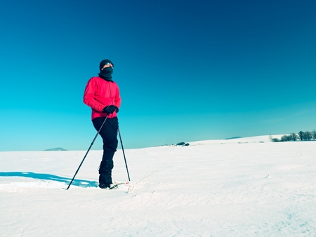 Winter tourist with snowshoes walk in snow drift. Hiker in pink sports jacket and black trousers trekking snowshoeing in powder snow. Sunny winter day, gentle wind Brings small snow flakes.