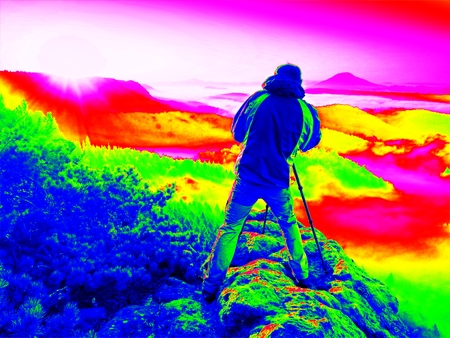 Ultraviolet  scan. Infrared  photo. Happy photo enthusiast  enjoy  photography of  fall daybreak in nature on cliff on rock. Dreamy foggy landscap