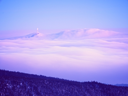 inverse: Far mountain peak with observatory above creamy mist. Shinning lights on antenna. Wavy fog in vally bellow, inverse winter weather. Stock Photo