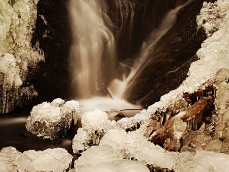 Frozen waterfall. Winter creek, icy stones and branches fallen into chilly water of mountain stream