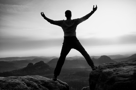 a situation alone: Happy man with raised arms gesture triumph he Exposed cliff. Satisfy Hiker silhouette on sandstone cliff watching down a hilly landscape. Stock Photo
