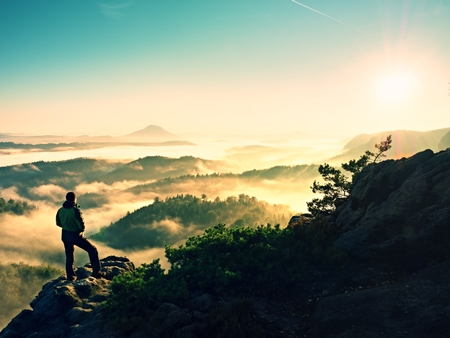 climbed: Man silhouette climbing high on cliff. Hiker climbed up to peak enjoy the view. Man watch over misty and foggy morning valley in morning Sun. Stock Photo