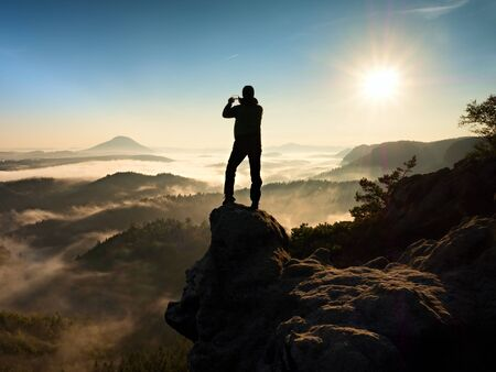 climbed: The man standing on a high cliff. Hiker climbed up a rocky peak and enjoy view this valley bellow. Man watch over misty and foggy morning valley in morning Sun. Stock Photo