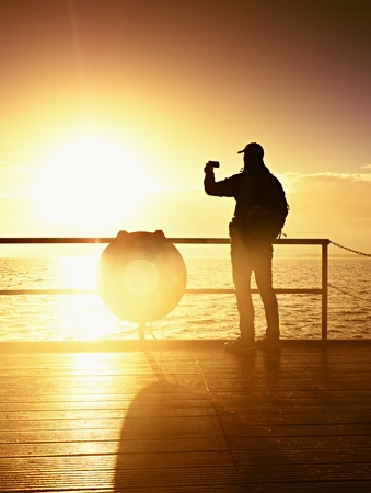 Tourist photograph  on sea mole. Hiker take photos of morning sea. Autumn fog. Tourist on wooden board in wharf, Sunny sky, smooth water level